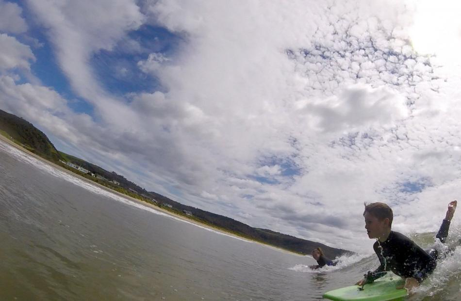 Zac McAuliffe (9) and his mother, Natalie Dilley, surf Curio Bay, the Catlins, on December 14....