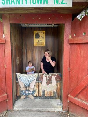 Tilly Price (2) and her mum, Alana, relax and read at Shantytown on the West Coast on January 2. Photo: Dom Price