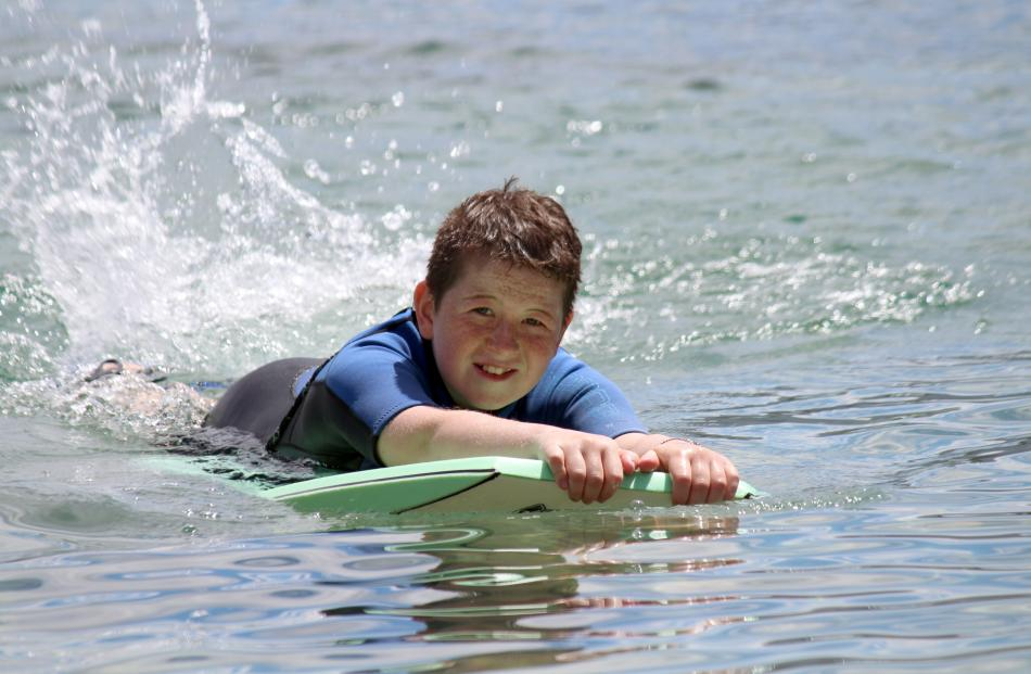 Brady Connelly (11) rides on a boogie board on a calm Lake Wanaka, on January 10. Photo: Garry...