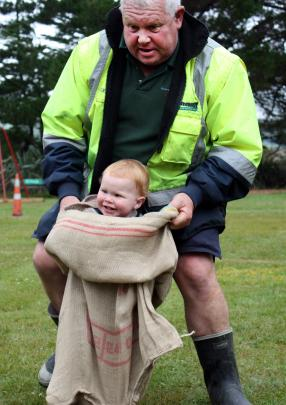 Toby Morris (1½) gets a helping hand from granddad Roger in the sack race at the Aramoana Family Fun day. Photo: Leah Nicol