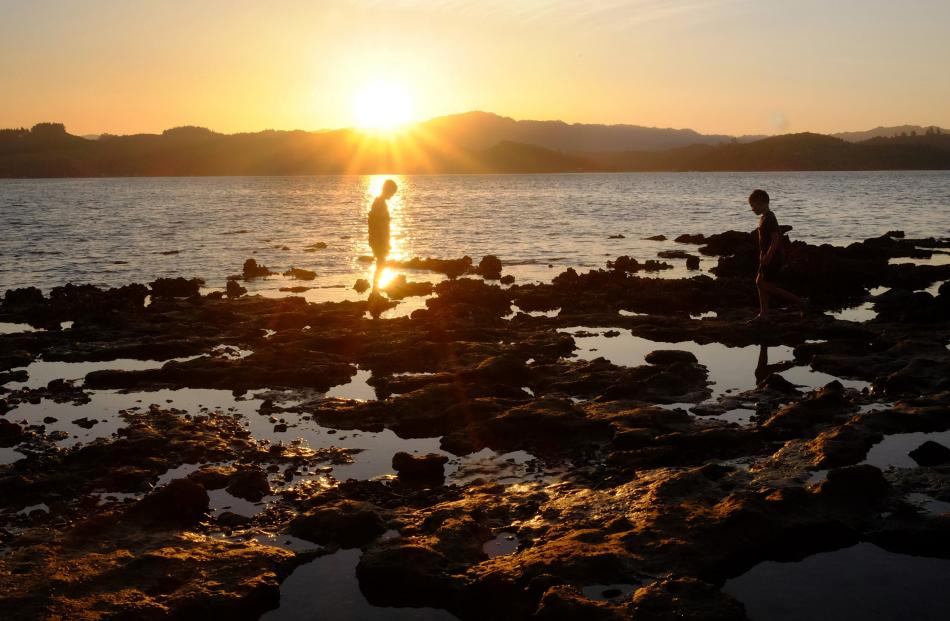 Daniel (10) and Luca (8) Ryan explore rock pools as the sun goes down at Puriri Bay, Northland....