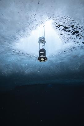 An acoustic doppler current profiler is suspended under the ice to measure currents from the...