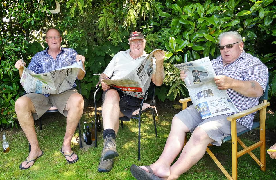 The lawns mowed and drinks poured, Geoff Davis, of Palmerston, John Rawson, of Oamaru, and Trevor Young, of Cromwell, take the chance to read the Otago Daily Times delivered to Te Anau. Photo: Lois Davis
