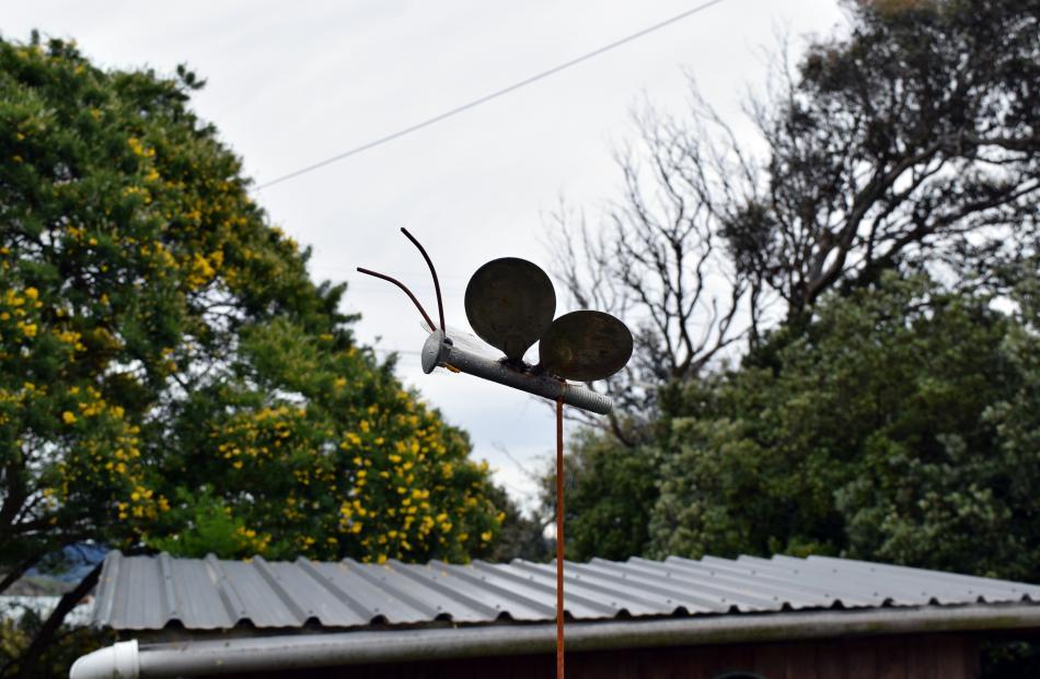 A butterfly sculpture flies above a chicken coop.
