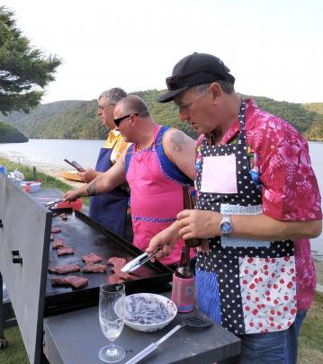 Lindsay Keith, Wayne Sheridan and Chris Keith cook on the BBQ for the Taieri Mouth cribbies on...