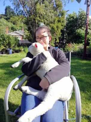 Cuddling happy lamb Lamington is Magic Moments winner Monica Homes, of Dunedin. PHOTOS: SUPPLIED