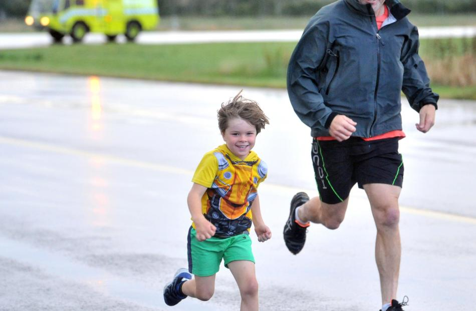 Oliver (5) and Tim Marshall, of Alexandra, are stride for stride down the runway.