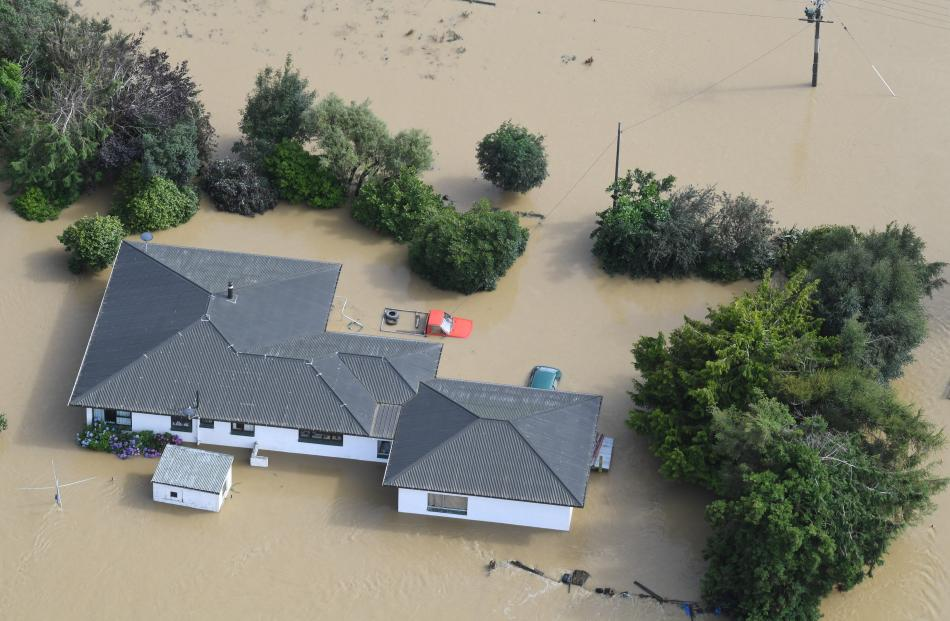 A utility vehicle sits in front of a flooded house, where it was left as the water rose.