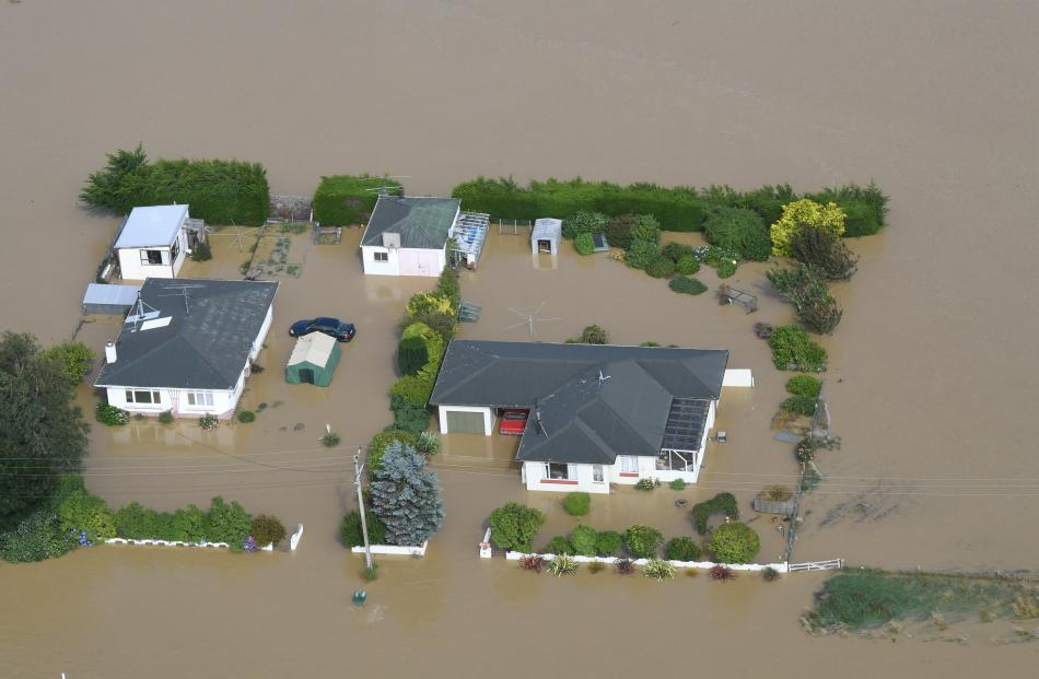 Sheds, cars and heavy machinery are swamped by the Mataura River on Wednesday.