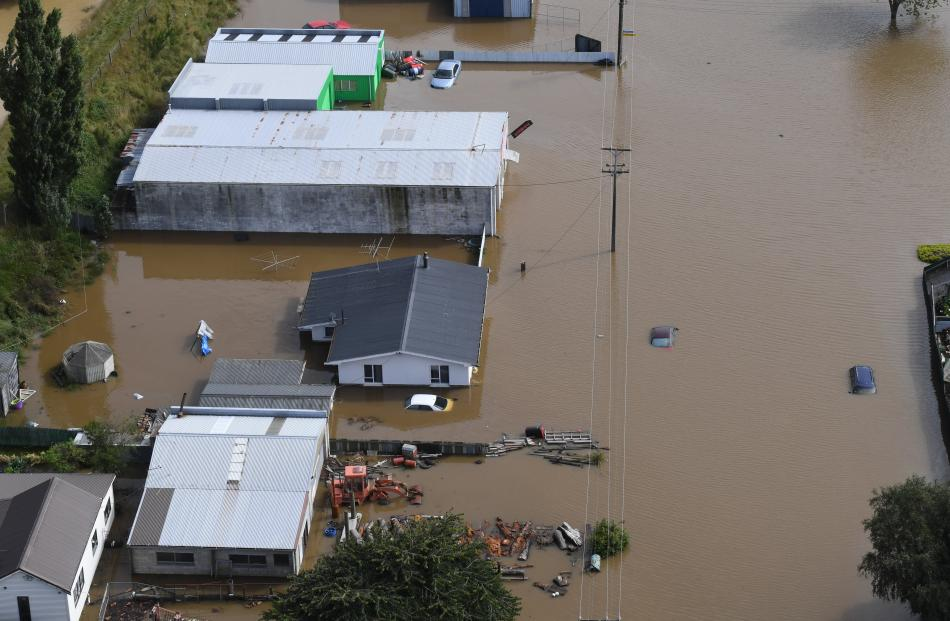 Muddy brown floodwater on Wednesday surrounds a farm that would otherwise be set in a sea of...