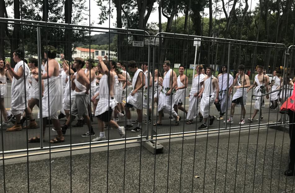 Students donning DIY togas on the street outside Fosyth Barr Stadium. Photo: Daisy Hudson