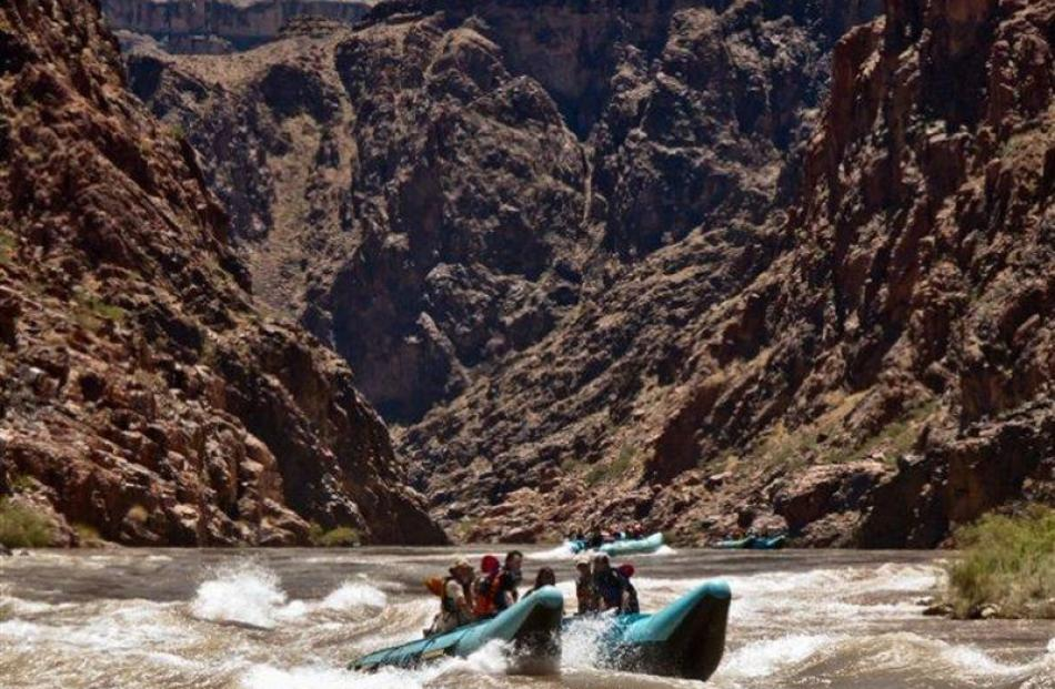 The 1500m-high cliffs of the Grand Canyon loom behind as a  boat prepares for another rapid,...