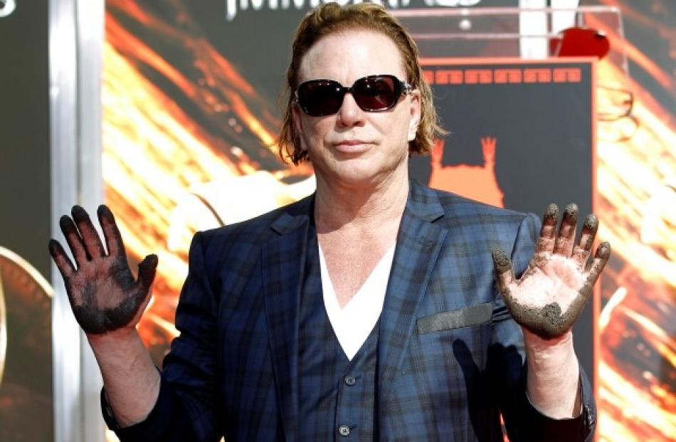 Actor Mickey Rourke shows off his hands after leaving his handprints in cement during a hand and...