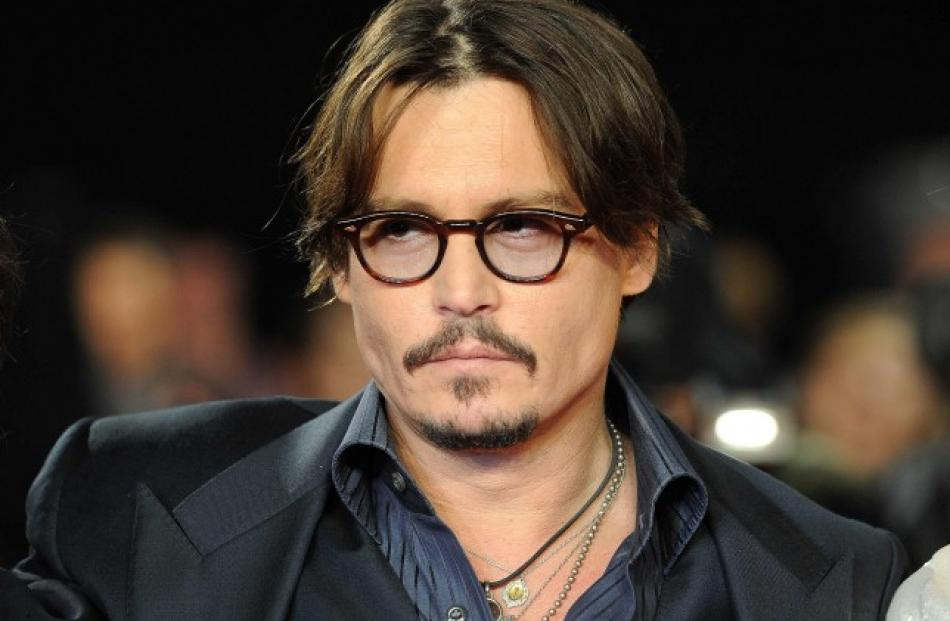 Johnny Depp poses for photographers as he arrives for the European premiere of 'The Rum Diary',...