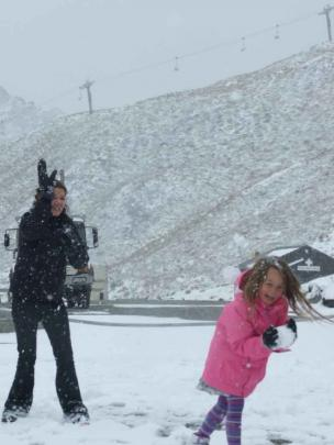 Emelia Thatcher (4), of Auckland, ducks a snowball from Melissa Parker, also of Auckland, keeping...