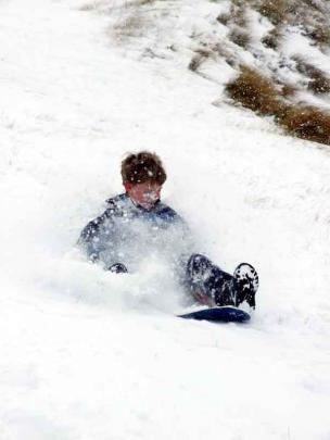 Ben Williamson (8), of Auckland, takes advantage of an abandoned snowboard at the Coronet Peak...
