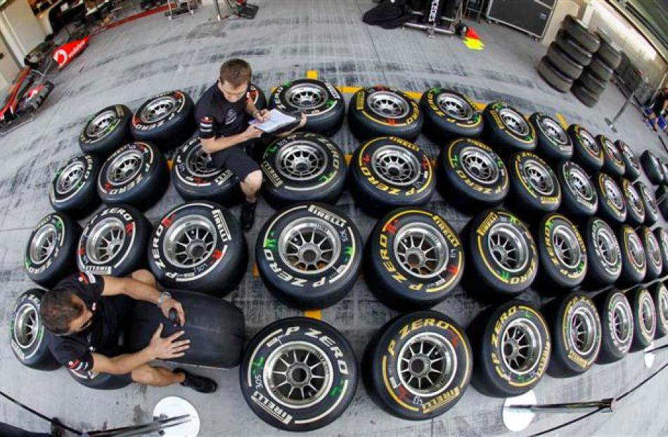Red Bull technicans mark tires and take notes in the pit-lane ahead of the Abu Dhabi F1 Grand...