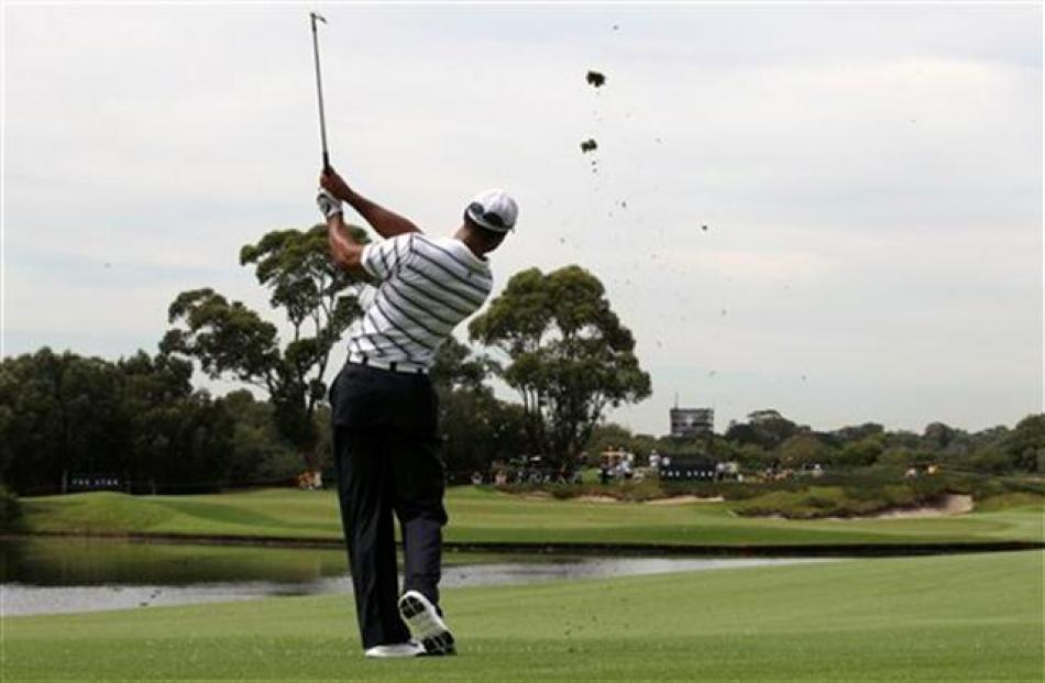 Tiger Woods plays a shot across a water hazard on the 14th during a pro-am event of the...