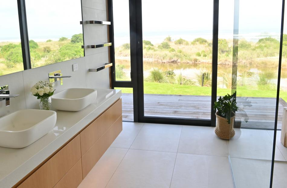 Like the rest of the house, the ensuite is all about the view. Electric blinds retract into the...