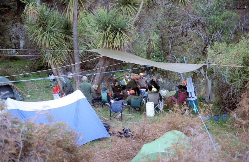 Members of the Wanaka Hunts course share stories under the base-camp tent-fly following a day's...