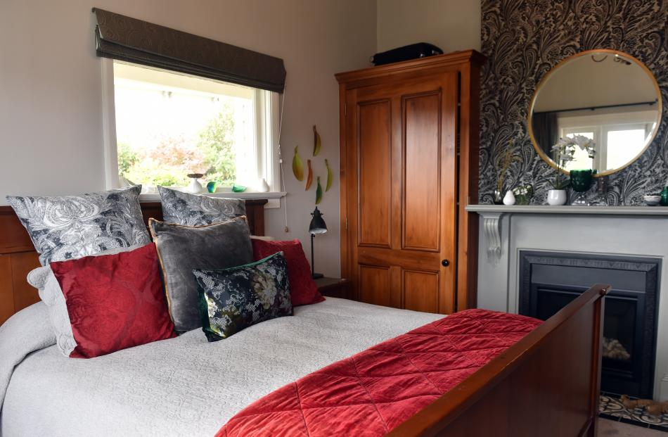 The gas fire in the master bedroom is surrounded by a painted wooden mantelpiece. The black...