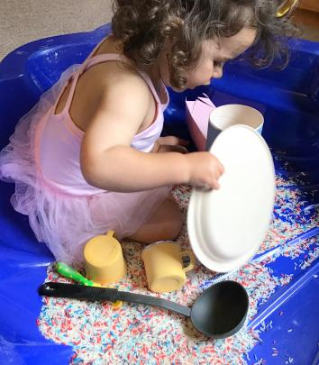 Madeline Gallagher (nearly 2) plays in the lounge with dyed rice, plates, cups and spoons....