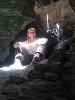 Project manager Tim Dennis rests in an extensive multi-roomed rock shelter used by early gold...