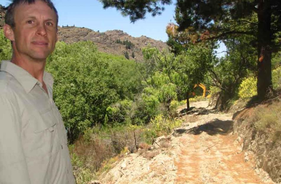 Mr Dennis stands on the trail while contractors work in the background to clear vegetation.