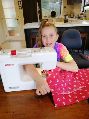 A stitch in time . . . Brooke Beaman (10) at home in Glenross stitches a new apron. PHOTO: Creina...