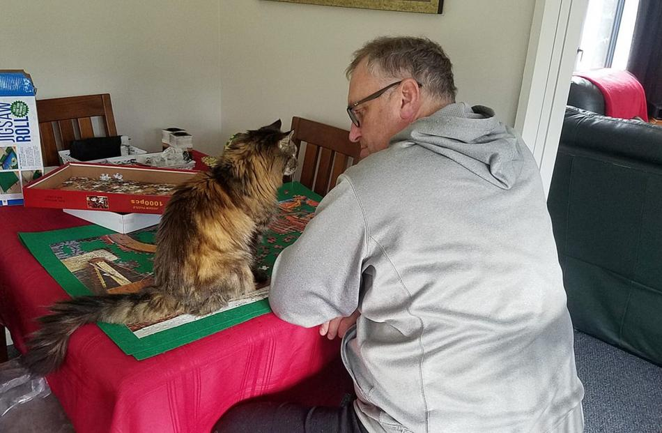 Purrrfect advice . . . Tony Heptinstall, of Dunedin, consults his puzzle assistant Willow for...