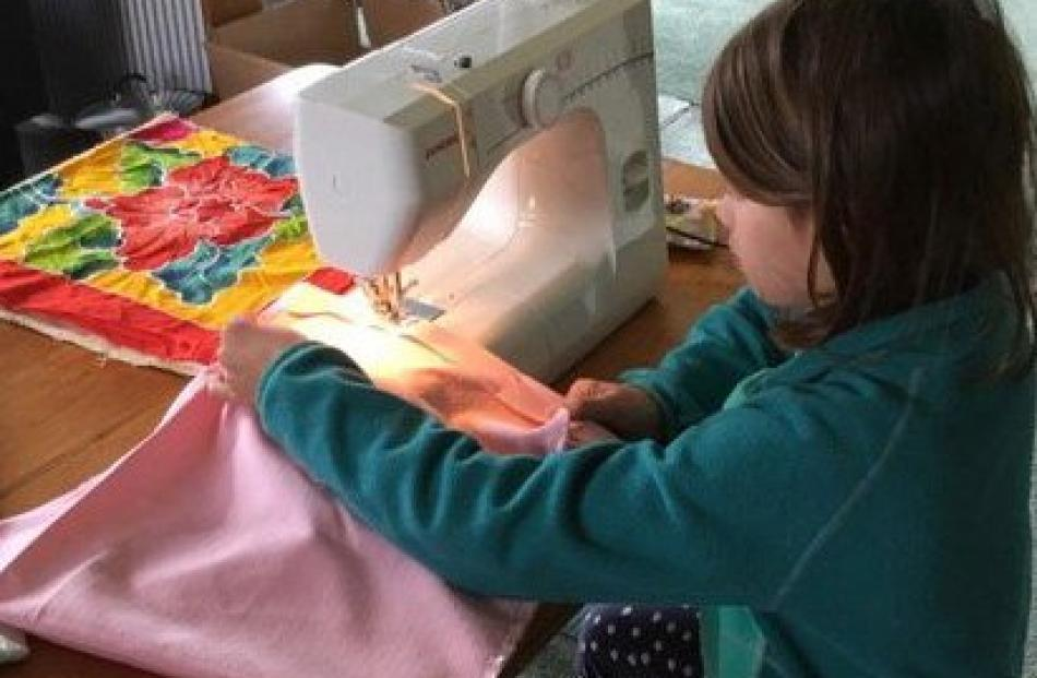 Bella McRitchie-King (8), of Stewart Island, sews ''boomerang'' shopping bags for the locals....