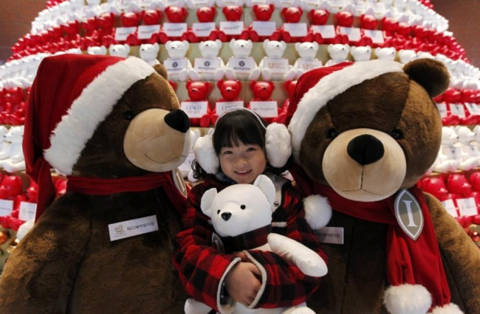 A girl poses for photographs in front of a Christmas tree decorated with Teddy bears at Grand...