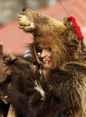 A man dressed in a bear costume takes part in a traditional fair for Christmas and New Year...