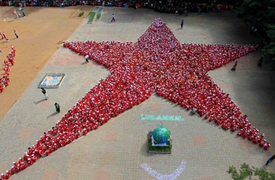Schoolchildren dressed as Santa Claus form the shape of a star at a school in the southern Indian...