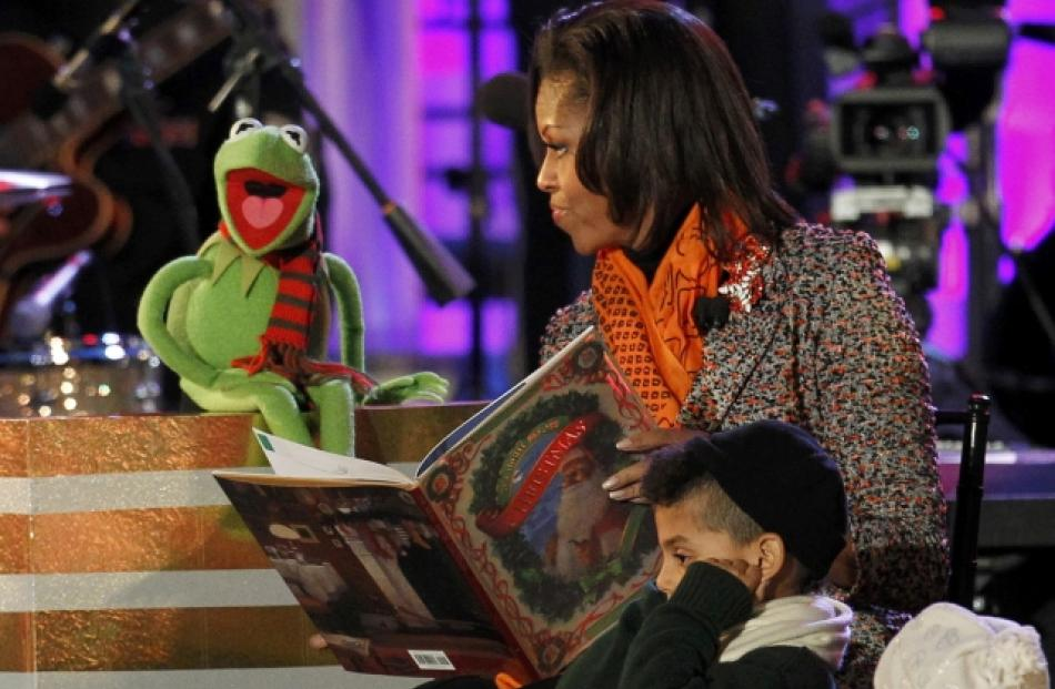 US first lady Michelle Obama reads a Christmas story to children with the help of Kermit the Frog...
