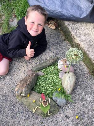 Liam Glover (5) is pleased with his frog on a rock creation in the garden. PHOTO: LYNETTE GLOVER
