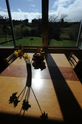 A restored kauri dining table catches the sunlight and rural vista from Jan and Roy Johnstone's...