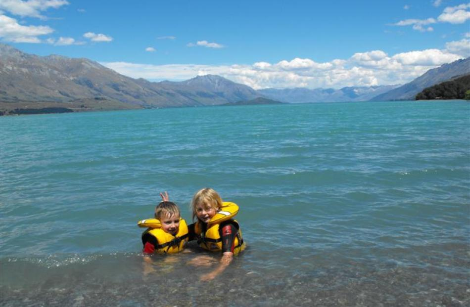 Lucy (8) and Sam Glover (5) sit at the head of Lake Wakatipu in Kinloch just before Christmas.