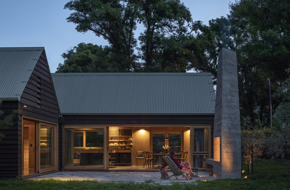 The tall chimney of the outdoor fire contrasts with the home's horizontal lines. The owners plan...