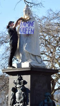 Dunedin protester Andrew Tait places a necklace of potatoes around the Queen Victoria statue at...