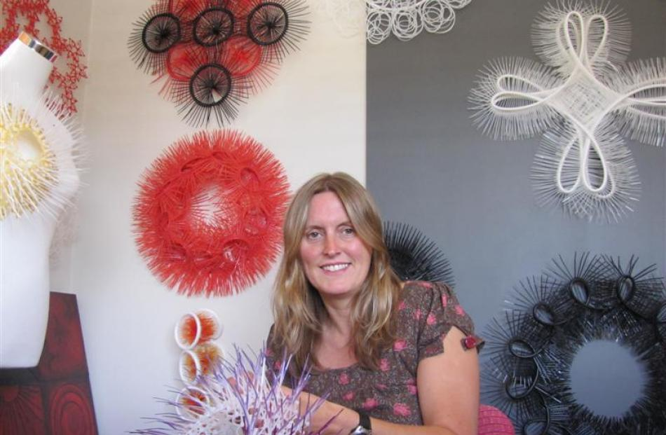 Wanaka artist Andi Regan (38) works on one of her cable-tie creations in her workshop. Photo by...