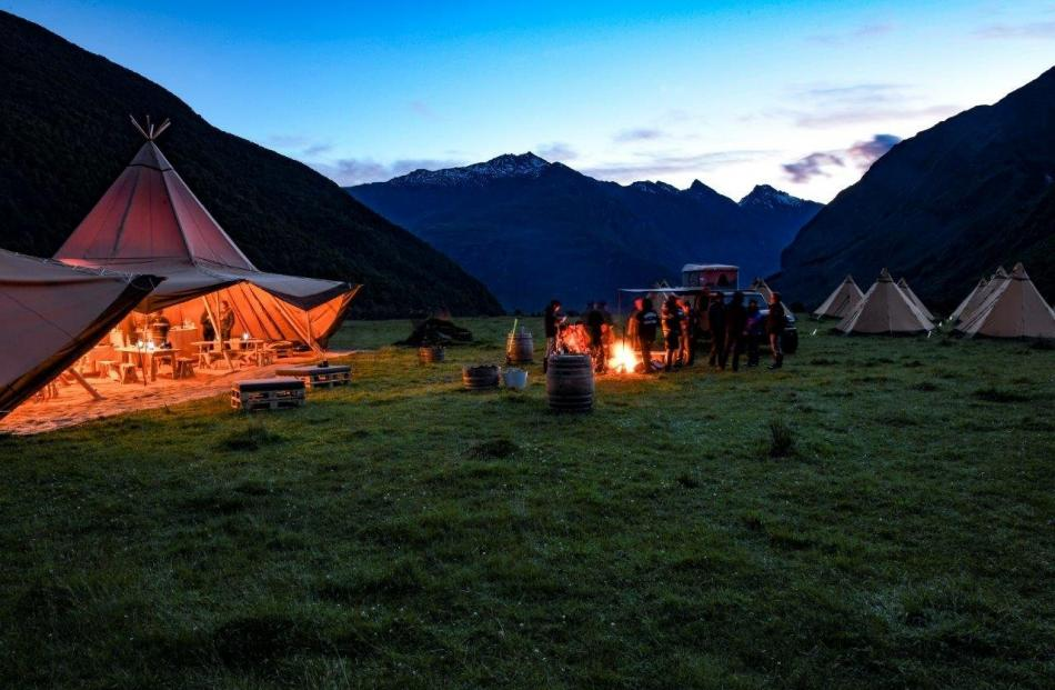New Zeal clients eating dinner cooked by an on-site chef in a giant Nordic tipi in a remote...