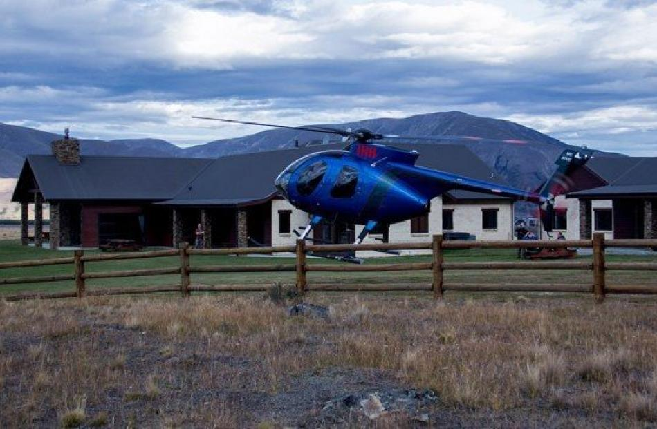 A helicopter transporting guests from Queenstown Airport to the NZ Hunting Lodge in the remote...