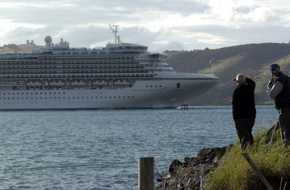 Two men watch the cruise ship Diamond Princess slip past Harington Point last week.