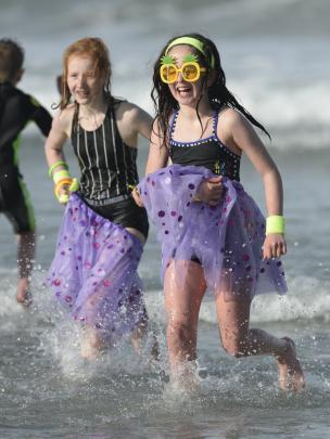 Ruby Nicolson (11) and Harlow La Hood (10) run from the surf after a chilly swim.