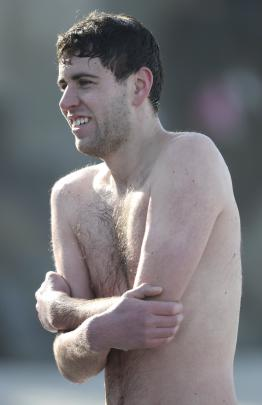 Lewis Forrester, of Dunedin, tries to warm up after his plunge.