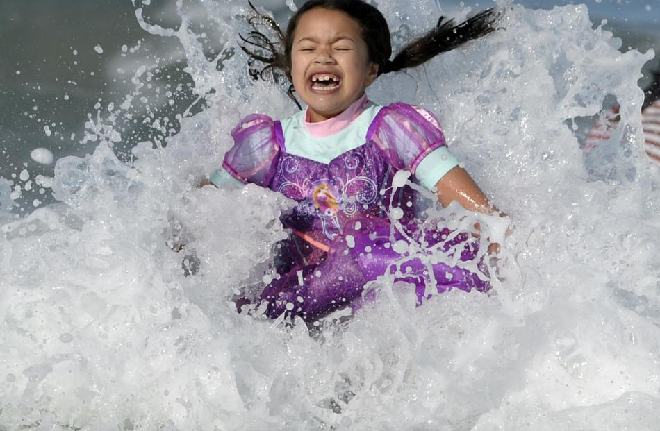 Jazz Fraser relishes the icy water during the Polar Plunge at St Clair Beach yesterday. PHOTOS:...