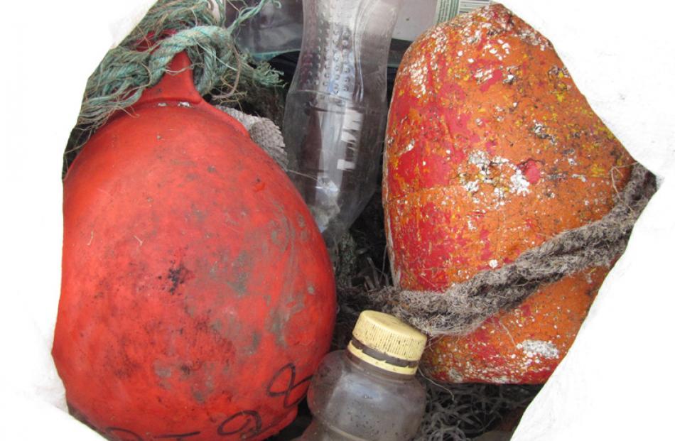 Plastic rubbish inside a fadge includes bright orange fishing floats.