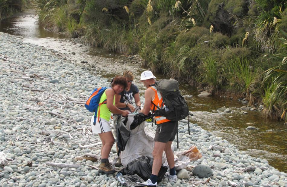 Marietta Gibb, Robyn Hoglund and Robin Manera fill a fadge with rubbish between Barn Bay and...