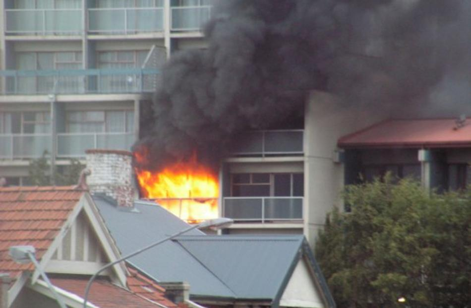 Flames erupt from the  third-floor room. Photo by David Winter